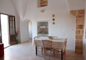 illuminato dalla unica luce salentina nella foto vediamo il tipico tavolo utilizzato in salento con parte di un antico camino