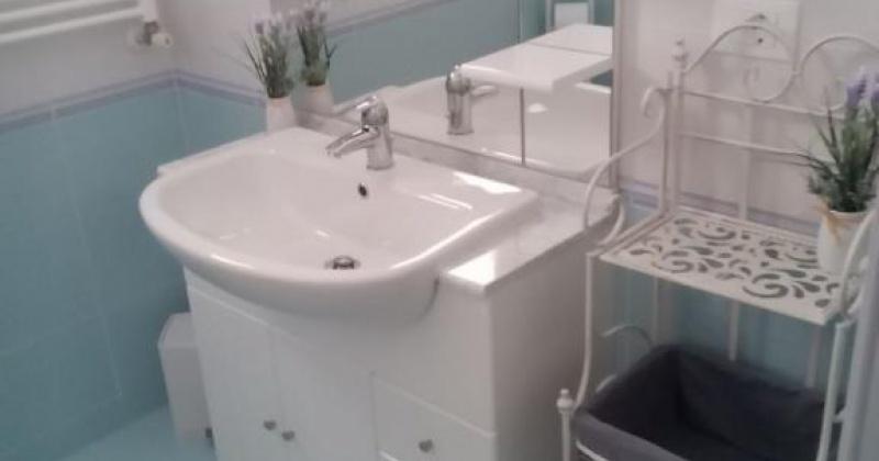nella foto vediamo un bagno con piastrelle color celeste e uno specchio