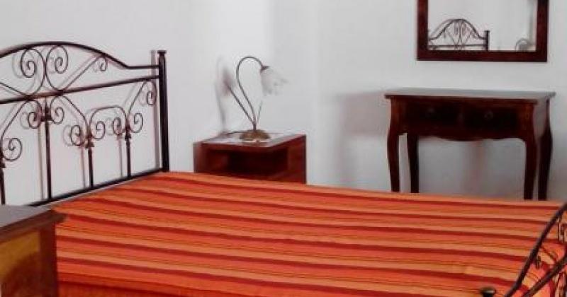 nella foto vediamo una camera da letto con un copriletto arancione di una casa in vendita a salve