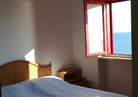 nella foto vediamo una camera da cui si vede il mare