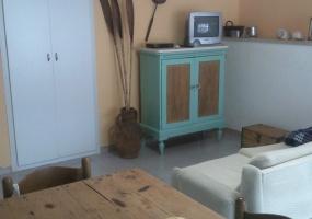 foto di parte del soggiorno arredata con mobili unici e colorati di verde acqua e legno naturale si trova in salento precisamente in Pescoluse di Salve